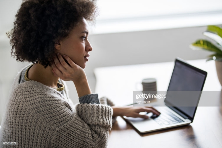 Profile view of pensive black woman using laptop and surfing the net at home.
