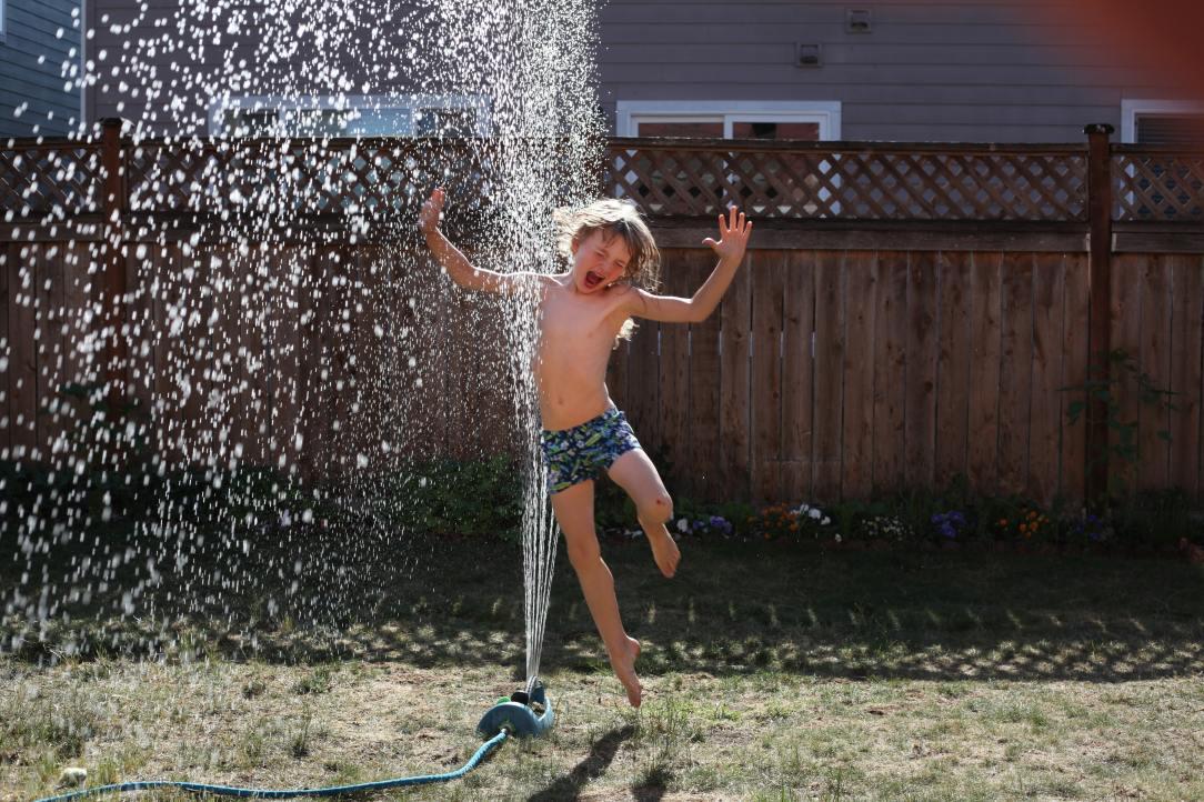 boy-jumping-near-sprinkler-1240950