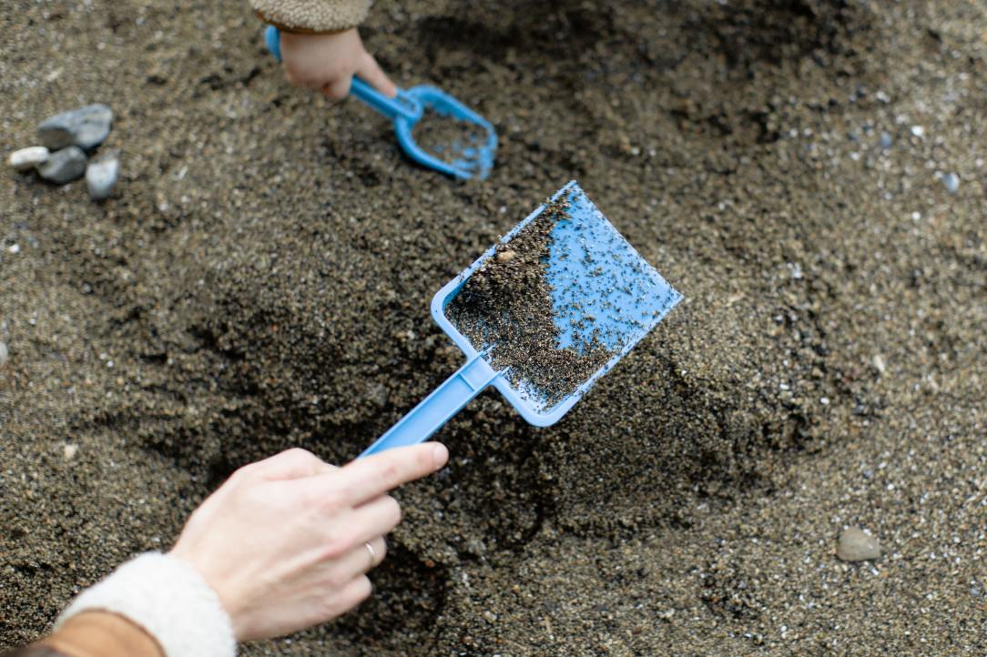 crop-faceless-mother-with-baby-playing-with-plastic-shovels-3932877