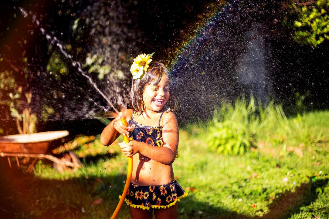 smiling-girl-playing-with-water-hose-2168791