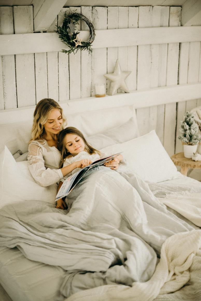 woman-and-girl-lying-in-bed-while-holding-book-3171116
