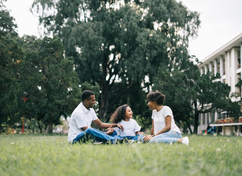 family-sitting-on-grass-near-building-1128316